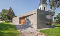 Abgeschirmt gegen die Straße, offen zur Kirche: das neue Pfarrzentrum von Glanhofen und St. Nikolai. / Bild: (c) Bauraum.architekten