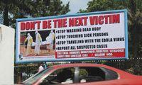 A car drives past a public health advertisement against the Ebola virus in Monrovia