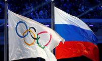FILE PHOTO: The Russian national flag and the Olympic flag are seen during the closing ceremony for the 2014 Sochi Winter Olympics