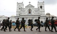 Soldiers and police officers walk past St. Anthony's Shrine in Colombo
