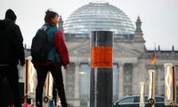 People walk past a temporary memorial, a column dedicated to the victims of the Holocaust, set up by activists of the 'Zentrum fuer politische Schoenheit' (Center for Political Beauty) in Berlin