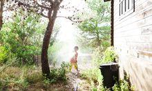Kind spielt mit Gartenschlauch