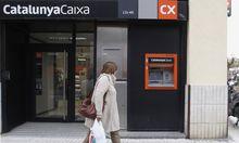 A woman walks outside a branch of nationalized savings bank Catalunya Caixa in Vilassar de Mar