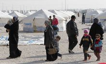 Syrian refugees walk near newly pitched tents at the Al-Zaatari refugee camp in Mafraq