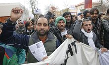 Refugees shout slogans during a protest by asylum seekers in the Austrian village of Traiskirchen