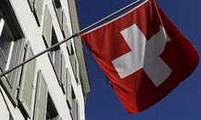 Switzerlands national flag is seen beside the logo of Swiss bank UBS in the town of Riehens national flag is seen beside the logo of Swiss bank UBS in the town of Riehen