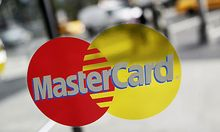 FILE- This Sept. 21, 2011, file photo. shows a MasterCard sign on a revolving door in New York. Maste