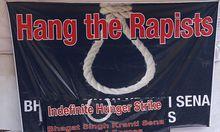 Ein Protest-Banner, das für einen Vergewaltiger Wirklichkeit wird, sollte ihn der Präsident nicht begnadigen.
