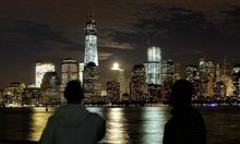 The moon rises behind the skyline of New York's Lower Manhattan and One World Trade Center in Jersey City