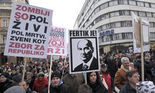 Protesters hold signs during an anti-austerity and anti-corruption protest in Ljubljana