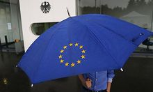 A person with an umbrella featuring the symbol of the European Union walks towards the interim facility of Germany's high constitutional court  in Karlsruhe