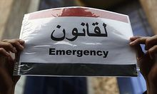 A protester displays a message on a placard of the Egyptian flag during a demonstration outside the p