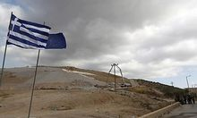 Municipality workers, right, block the entrance of a landfill outside Athens, as Greek and EU flags a