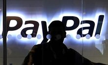 FILE - In this March 17, 2010 file photo, a PayPal employee walks past the PayPal logo at the interna