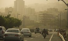 Motorists travel on a highway in Tehran as the city is covered in dust