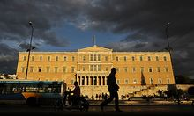 A man walks as vehicles drive in front of the  Greek Parliament, on Wednesday, Sept. 21, 2011. Greece