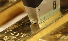 An employee of Deutsche Bundesbank uses metal analysis device on gold bar during a news conference in Frankfurt