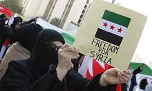 A protester holds a placard as she protests outside the UN House in Manama