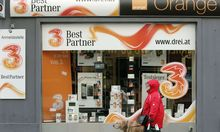 A woman and her dog walk by a telecommunications store advertising 'Orange' and '3' in Vienna