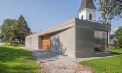 Abgeschirmt gegen die Straße, offen zur Kirche: das neue Pfarrzentrum von Glanhofen und St. Nikolai.