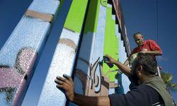 Ein Akt wider die Symbolik: Der Künstler Enrique Chiu besprüht den Zaun.  / Bild: Reuters