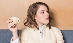 Sophie Stockinger trägt ein Kleid und einen Mantel von Jil Sander.  Die Aufnahmen entstanden im Café Weidinger am Lerchenfelder Gürtel. / Bild: (c) Foto: Carolina Frank, Produktion: Daniel Kalt und Barbara Zach
