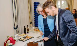 Nathan Trent schneidet beim Empfang in der Österreichischen Botschaft eine Torte an. Neben ihm: Botschafterin Hermine Poppeller