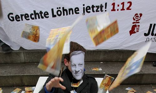 A member of the Juso wearing a mask with Vasella portrait throws fake banknotes during a demonstration before Swiss drug maker Novartis annual shareholders general meeting in Basel