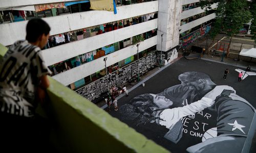 A man looks at a mural in memory of Kobe Bryant and his daughter Gianna, painted hours after they died in a helicopter crash, on the basketball court of a housing tenement in Taguig City
