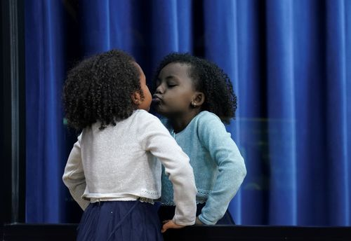 Girl kisses her reflection as Trump speaks at child care and paid leave summit at the White House in Washington