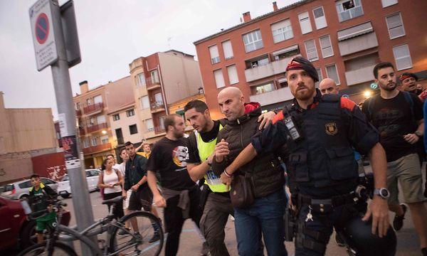Zivil gekleidete Beamte der Guardia Civil werden von lokalen Mossos-Polizisten aus einem Hotel in Calella eskortiert. / Bild: APA/AFP/JORDI BORRAS