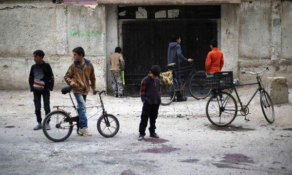 Syrische Kinder nahe der bombardierten Volksschule  / Bild: APA/AFP/AMER ALMOHIBANY