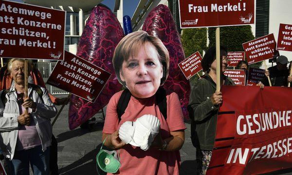 Ein Demonstrant in Berlin, verkleidet als Angela Merkel, verteilte vor dem gestrigen Dieselgipfel Mundschutzmasken. / Bild: (c) APA/AFP/JOHN MACDOUGALL