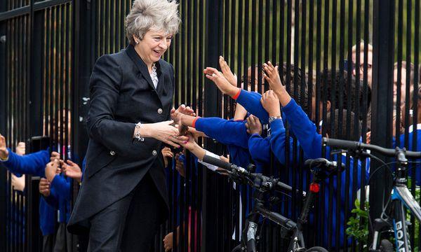 Die britische Regierungschefin Theresa May schüttelt Kindern die Hand. Parteiintern wollen nicht alle ihr die Hand reichen. / Bild: (c) APA/AFP/POOL/GEOFF PUGH (GEOFF PUGH)