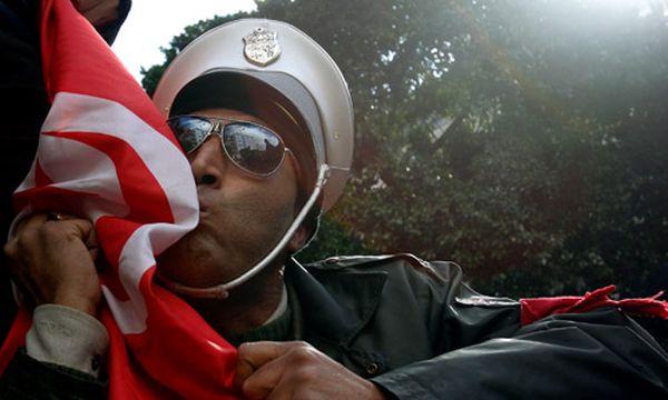 Tunesien ersetzt Gouverneure aller 24 Regionen / Bild: Tunesischer Polizist küsst die Flagge seines Landes (c) AP (Christophe Ena)