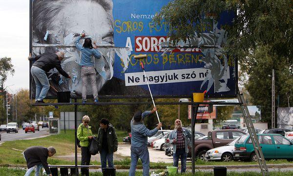 Oppositionsmitglieder entfernen ein Plakat der Anti-Soros-Kampagne. / Bild: REUTERS/Bernadett Szabo