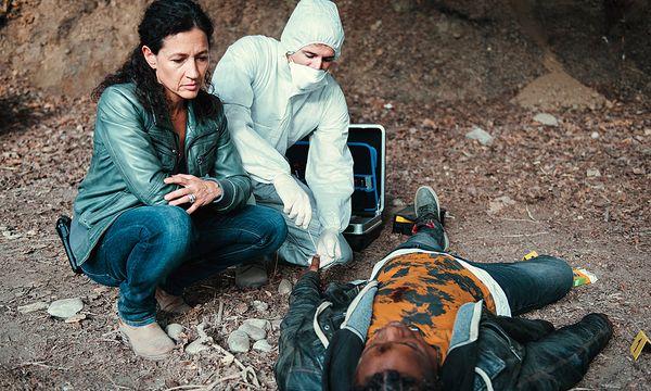 Kommissarin Liz Ritschards (Delia Mayer) und ein Kollege von der Spurensicherung untersuchen die Leiche des jungen asylsuchenden Ebi Osodi (Charles Mnene) / Bild: (c) ORF (SRF/Daniel Winkler)