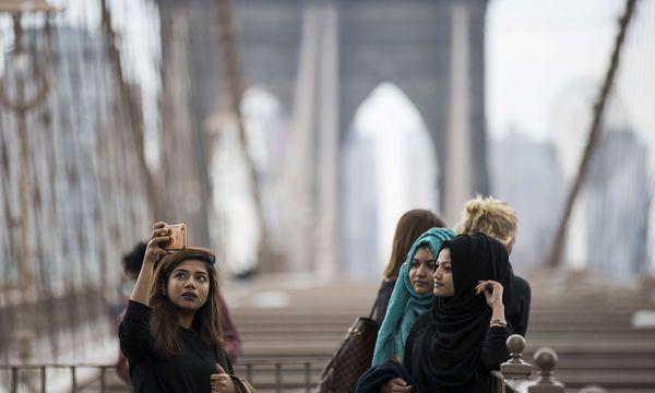 Erinnerungsfoto an der Brooklyn Bridge in New York. Der Tourismus aus dem Nahen Osten in die USA ist zurückgegangen.  / Bild: (c) AFP