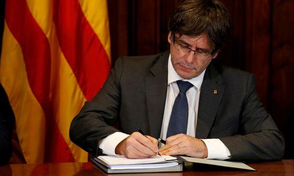 Carles Puigdemont, der katalanische Regionalpräsident, unterzeichnet den Beschluss zur Durchführung eines Unabhängigkeitsreferendums am 1. Oktober. Verflogen ist in Katalonien die demonstrative Eintracht angesichts des Terrors in Barcelona. / Bild: (c) REUTERS (ALBERT GEA)
