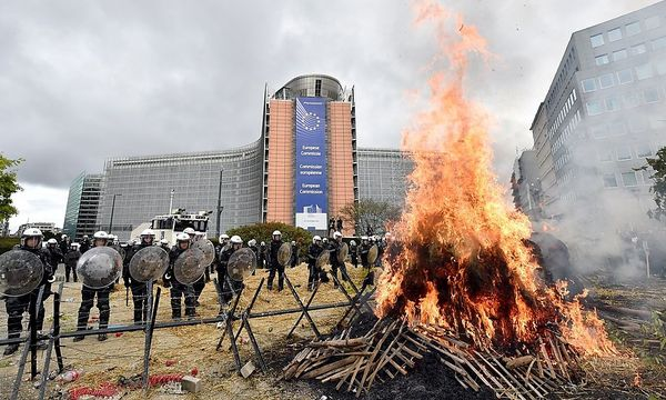 Police officers stand guard as farmers and dairy farmers from all over Europe take part in a demonstration in Brussels / Bild: REUTERS