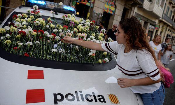 Blumen für die Mossos: Eine Unterstützerin der katalanischen Polizei am Sonntag in Barcelona. / Bild: (c) APA/AFP/JOSEP LAGO