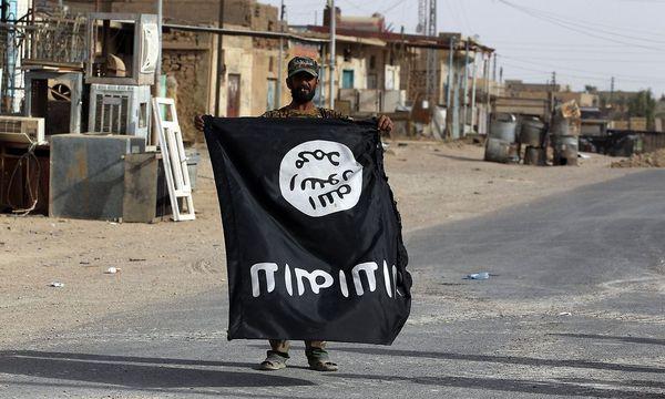 In irakischer Kämpfer zeigt in al-Qaim eine verkehrt gehaltene Flagge des IS in die Kamera, nachdem die Jihadisten aus der Stadt vertrieben wurden. / Bild: APA/AFP/AHMAD AL-RUBAYE