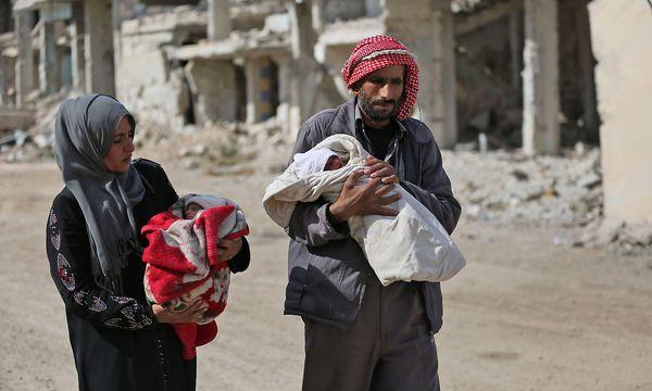 Eine Familie in der kürzlich von Rebellen befreiten Stadt Ost-Ghouta. / Bild: APA/AFP/AMER ALMOHIBANY