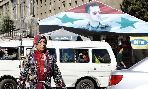 Eine Frau vor einem Assad-Banner in Damaskus. / Bild: APA/AFP/LOUAI BESHARA