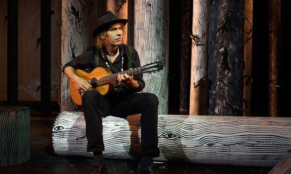 Ernst Molden im Wald von Mayerling, wie er auf der Bühne des Rabenhoftheaters umgesetzt wurde. Die Gitarre sei eine Zeitgenossin von Kronprinz Rudolf, erzählt Molden begeistert. / Bild: Clemens Fabry