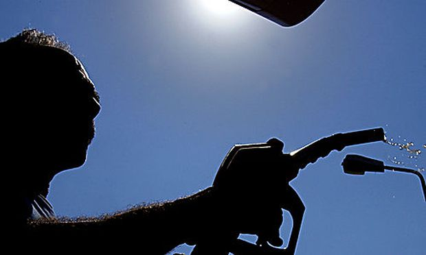 An employee of a petrol station holds a petrol pump after filling up a car in capital of Nicosia, Cyp