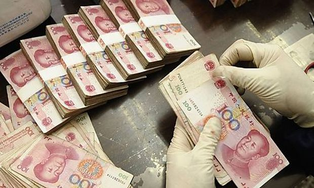 An employee counts yuan banknotes at a Bank of China branch in Changzhi