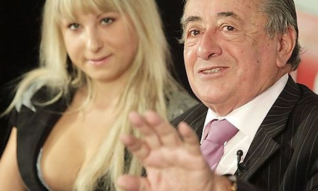 Austrian businessman Lugner gestures next to his girlfriend Anastasia during a news conference in Vie