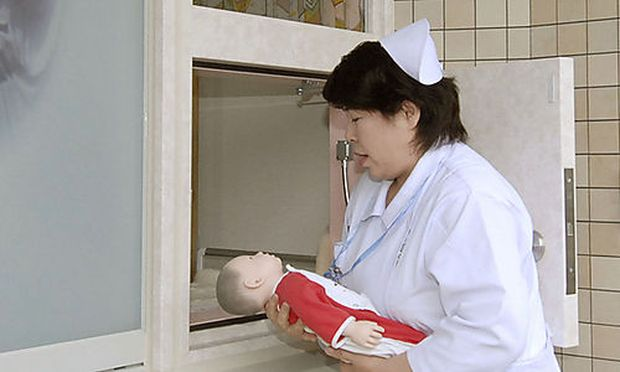 A nurse carrying a baby doll demonstrates the Jikei Hospitals baby drop-off system as the new proceds baby drop-off system as the new proced