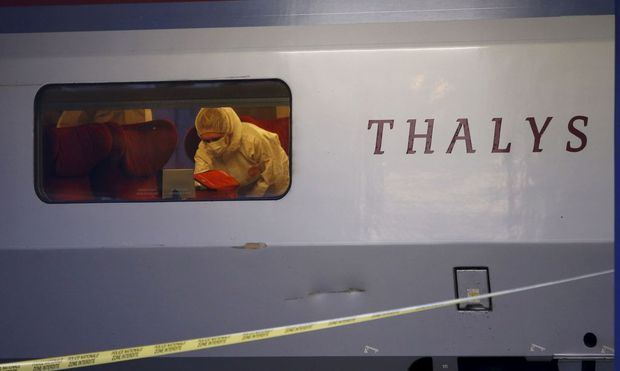 French investigating police in protective clothing collect clues inside the Thalys high-speed train where shots were fired in Arras